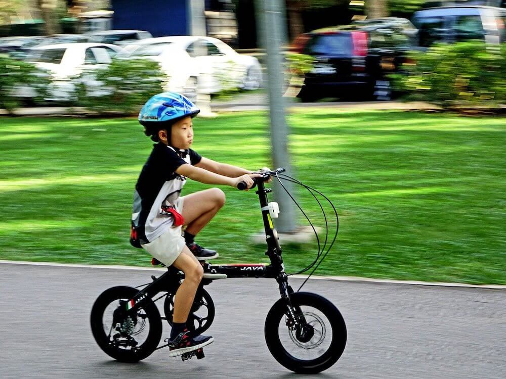 Toddler on tricycle with bike helmet