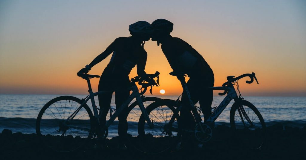Two cyclists kissing during a sunset