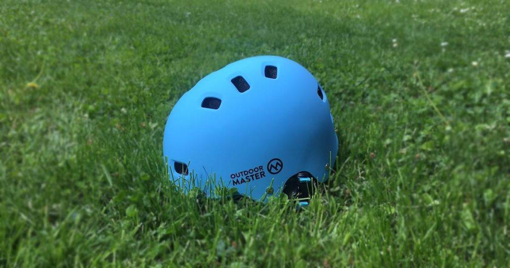 OutdoorMaster Skateboard Style Helmet in on a lawn