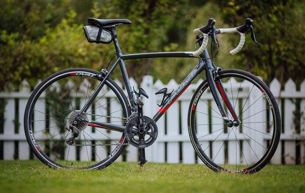 Aluminum road bike in grass in front of white fence