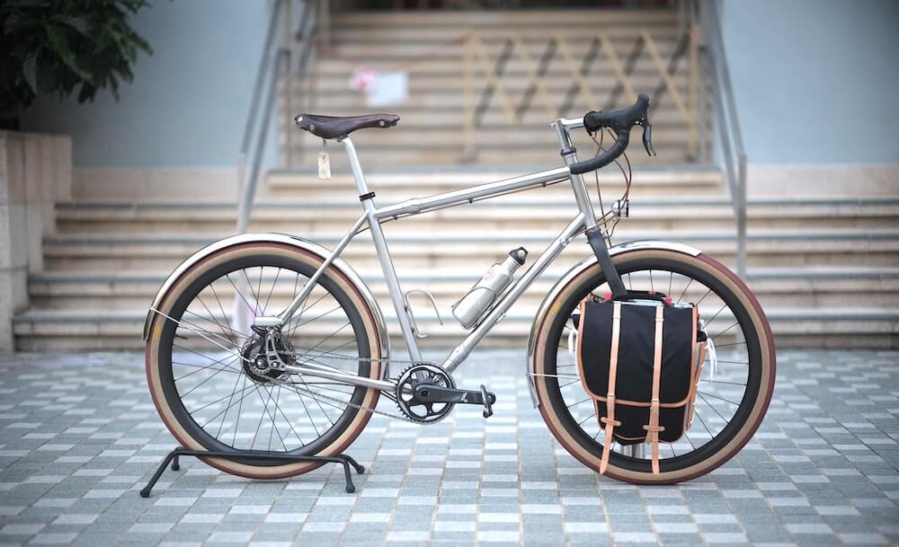 Titanium road bike in front of stairs with a black backpack on front fork